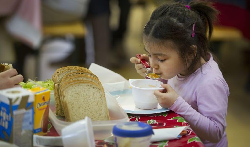 Een leerling luncht op basisschool Spaarndammerhout in Amsterdam.  (beeld Krijgen of de Broodtrommel is Gevuld met Ongezond Voedsel. anp / Evert Elzinga)
