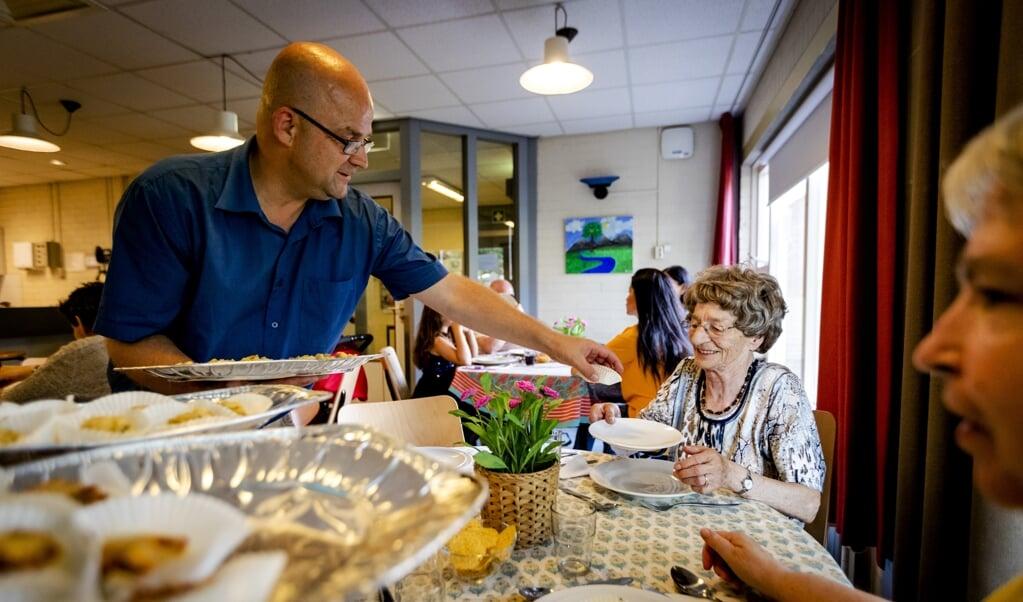 Een vrijwilliger deelt maaltijden uit aan minderbedeelden in Utrecht.  (beeld anp / Robin van Lonkhuijsen)