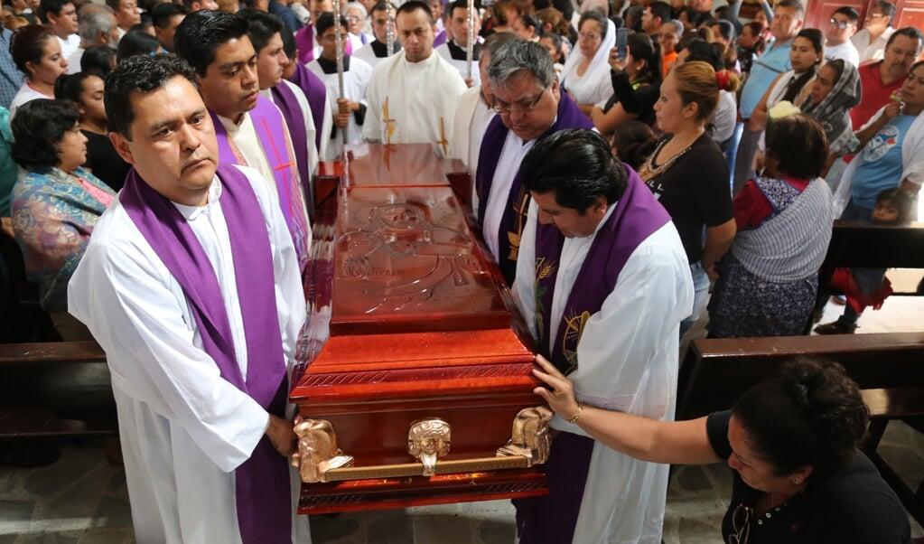 Mexicaanse priesters begraven een andere priester die omkwam bij de aanval van een gewapende bende. Drugskartels vormen in het land een grote bedreiging voor kerkleiders.  (beeld afp / Jesus Guerrero)