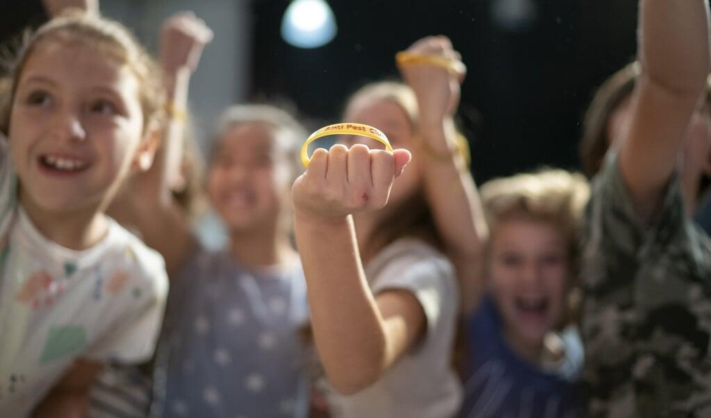 Kinderen tonen een antipestbandje tijdens de aftrap van de Week Tegen Pesten.  (beeld anp / Jasper Juinen en Tessa Posthuma de Boer)