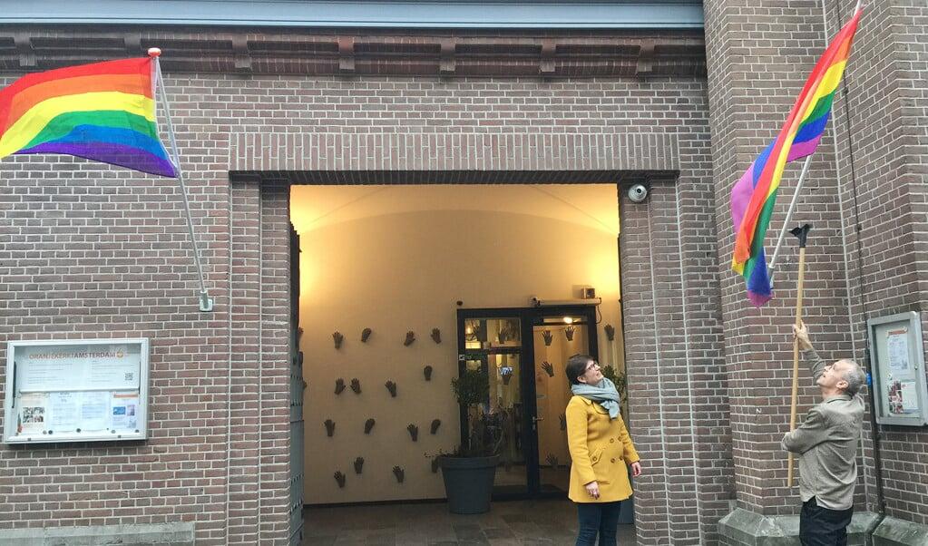 Kerkleden hijsen de regenboogvlag als teken van acceptatie van lhbt'ers, in Amsterdam.  (beeld protestantse kerk amsterdam)