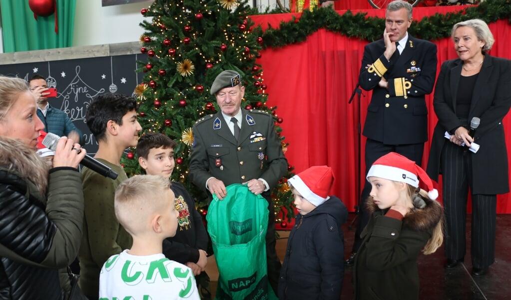Defensieminister Ank Bijleveld (rechts) en de Commandant der Strijdkrachten Rob Bauer nemen kaarten van scholieren in ontvangst.  ( beeld Riekelt Pasterkamp)