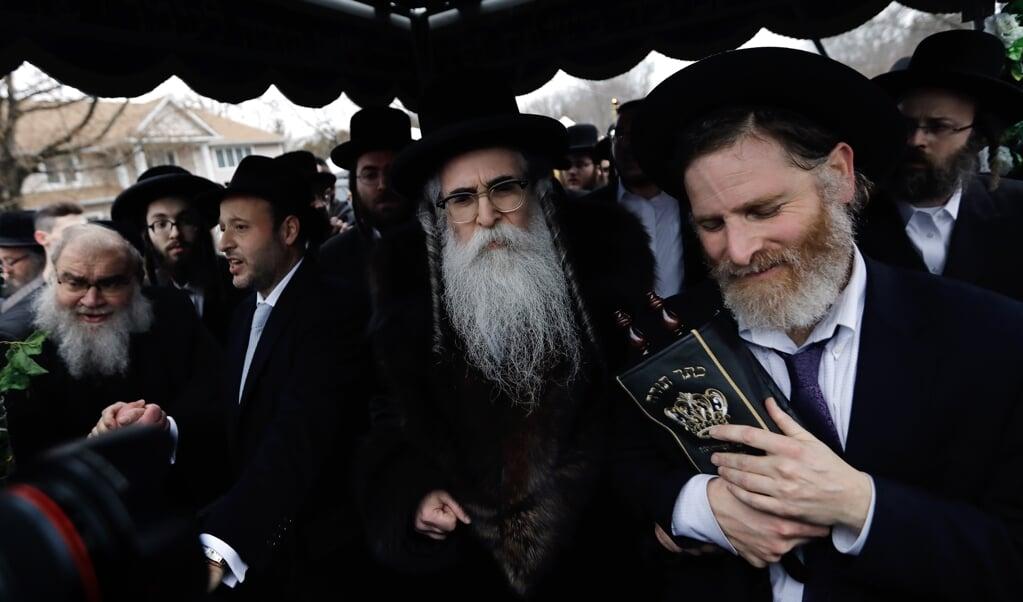 Rabbijn Chaim Rottenberg (midden, met grote baard) tijdens een ceremonie in Monsey, zondag.  (beeld EPA/PETER FOLEY)