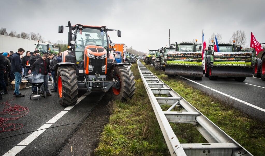 Op de A1 bij De Lutte vlakbij de Duitse grens blokkeerden protesterende bouwers en boeren beide kanten van de snelweg.   ( beeld anp / Vincent Jannink)