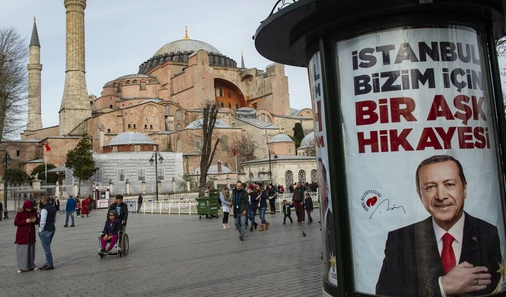 De Hagia Sophia in Istanbul met een verkiezingsposter van president Recep Tayyip Erdogan in maart 2019. 'Istanboel is een liefdesverhaal voor ons', zegt de slogan.  (beeld Yasin Akgul / AFP)