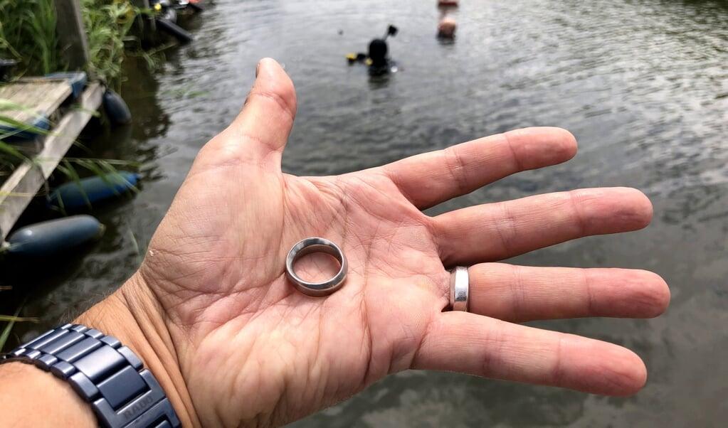 Deze ring werd opgedoken. Op de achtergrond de duiker die de ring gevonden heeft.   (beeld Gevonden-verloren)