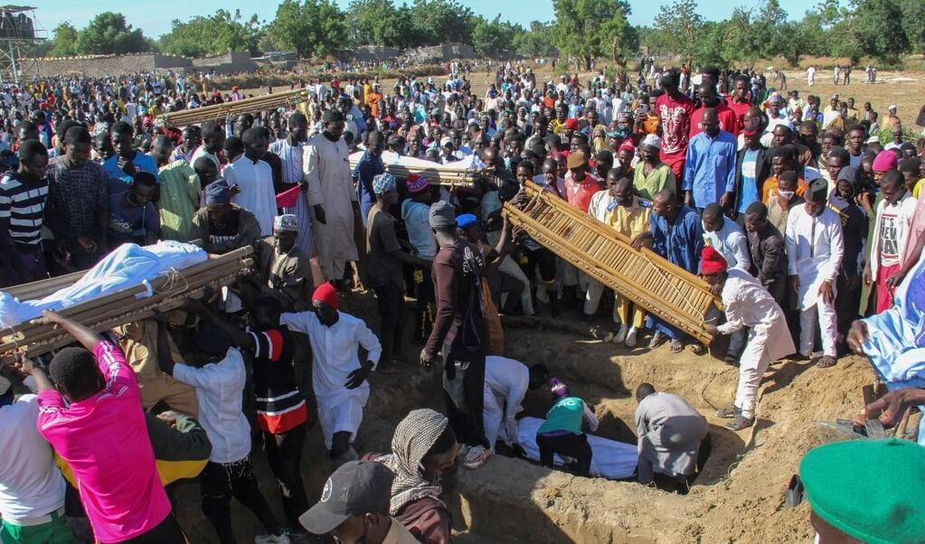 Zondag werden de eerste 43 vermoorde landarbeiders in Zabarmari begraven. Ze kwamen uit de deelstaat Sokoto, duizend kilometer verderop in het noordwesten van Nigeria.   (beeld afp / Audu Marte)