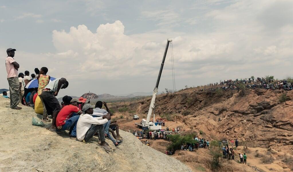Omstanders kijken naar de reddingswerkers die proberen water uit de schacht te pompen om de mijnwerkers te bereiken.  (beeld afp / Jekesai Njikizana)