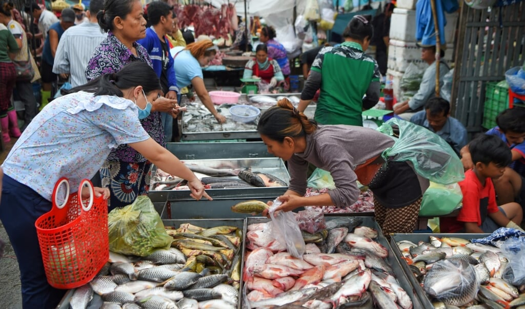 Op de Orussey-markt in het centrum van Phnom Penh drommen de mensen als vanouds samen.  (beeld afp / Tang Chhin Sothy)