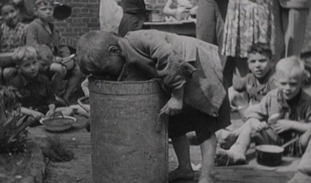 Een jongetje zoekt naar eten. Still uit de film Oorlog in Den Haag - Gefilmd Verleden 1940-1945  (beeld Haags Gemeentearchief)