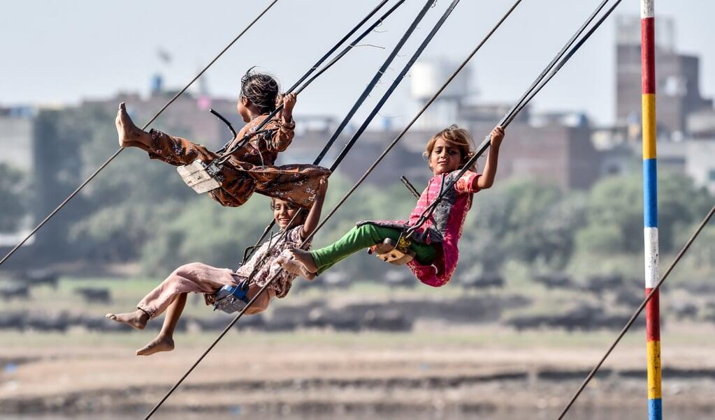 Meisjes op de schommel in Lahore, Pakistan.  (beeld afp / Arif Ali)