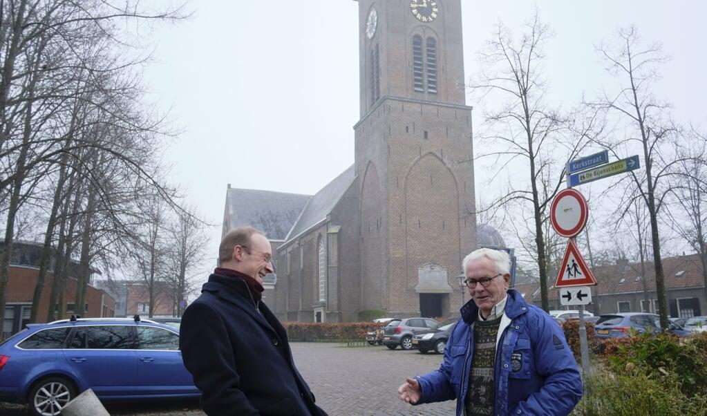 Dominee Krijn Hage (l.) in gesprek met zijn buurman. Op de achtergrond de Pieterskerk.  (beeld Dick Vos)