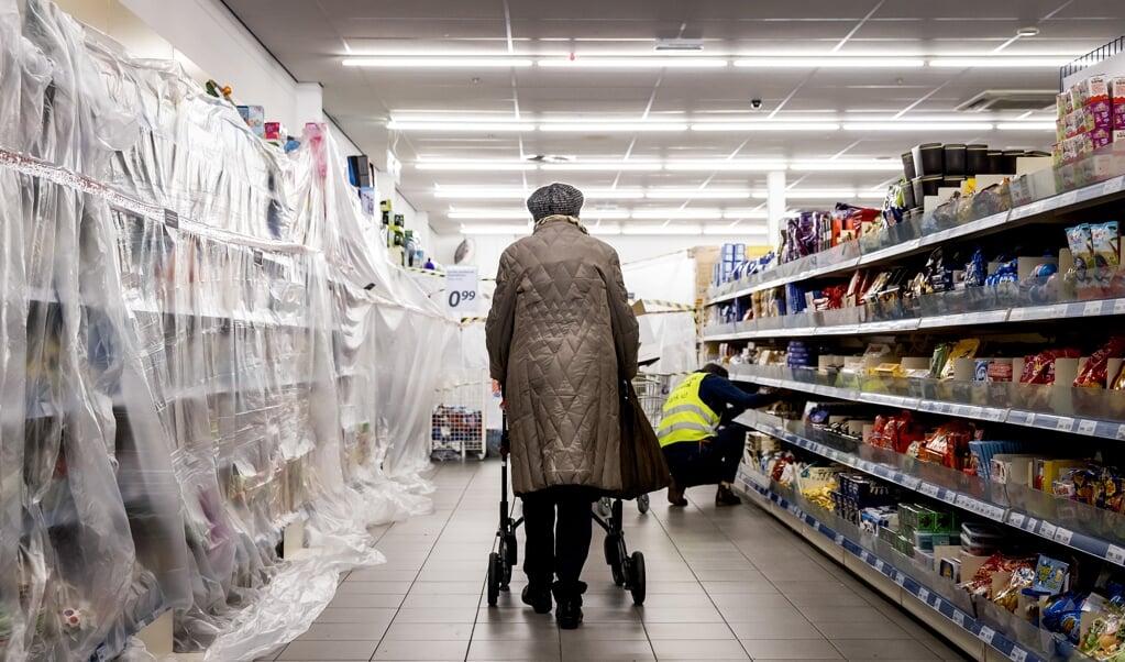 Een van de eerste klanten in de Action na de opening van een filiaal. De ruim vierhonderd winkels van de budgetketen in Nederland openden in eerste instantie weer hun deuren voor klanten. Die konden bij de budgetketen uitsluitend terecht voor producten die als essentieel worden beschouwd, zoals schoonmaakmiddelen, hygiëneproducten en etenswaren.  (beeld anp / Koen van Weel)