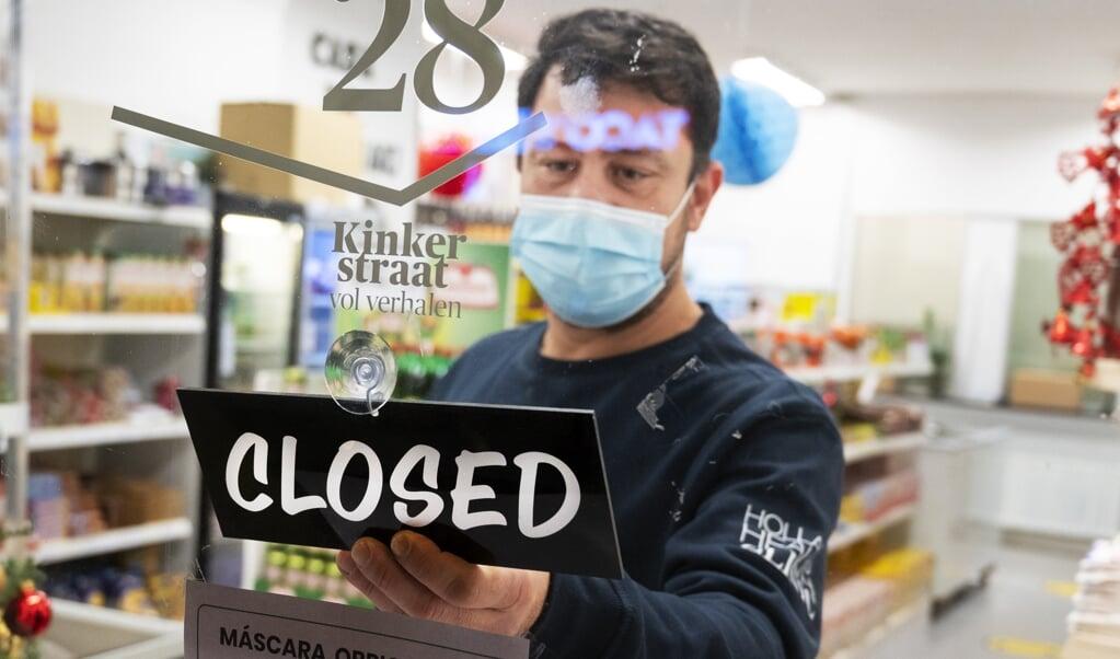 AMSTERDAM - Een winkelier sluit zijn zaak. Het kabinet wil winkels, scholen en contactberoepen sluiten om een einde te maken aan de forse stijging van het aantal nieuwe coronabesmettingen. ANP EVERT ELZINGA  (beeld anp / Evert Elzinga)