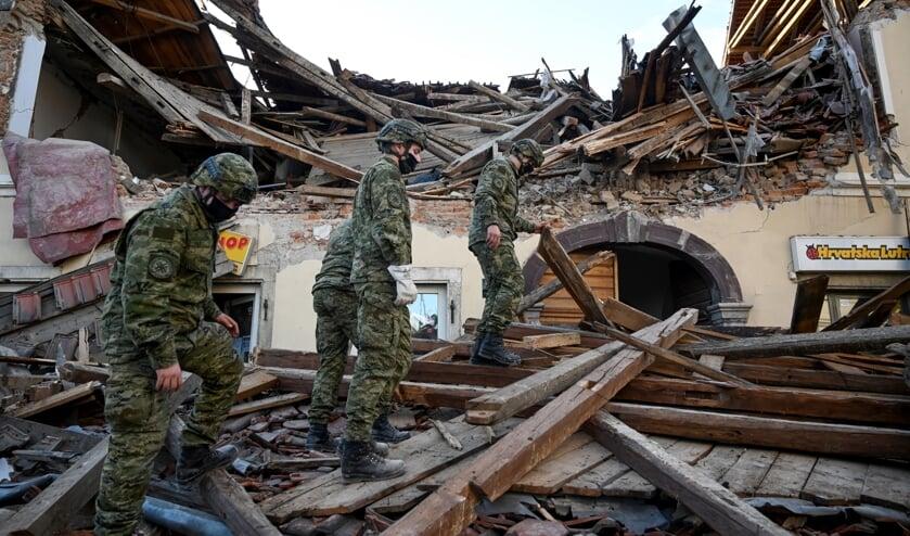 Soldaten zoeken in Petrinja tussen het puin naar overlevenden van de aardbeving. De regio bij Zagreb is getroffen door een zware beving.  (beeld afp / Denis Lovrovic)