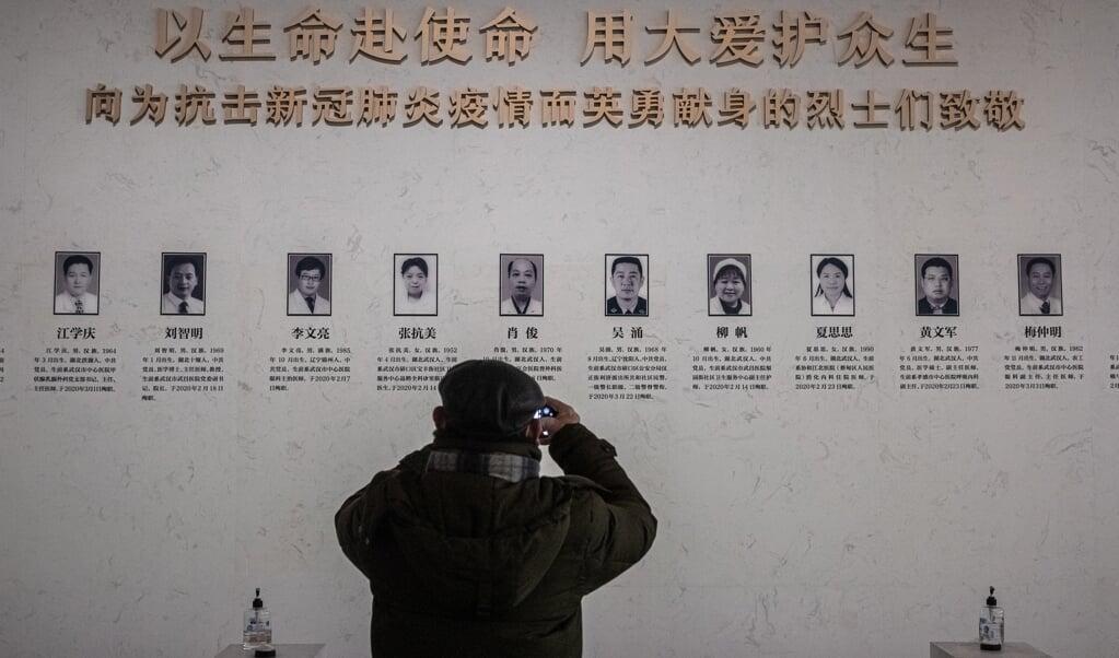 Een bezoeker van de tentoonstelling over de coronapandemie in Wuhan.  (beeld epa / Roman Pilipey)