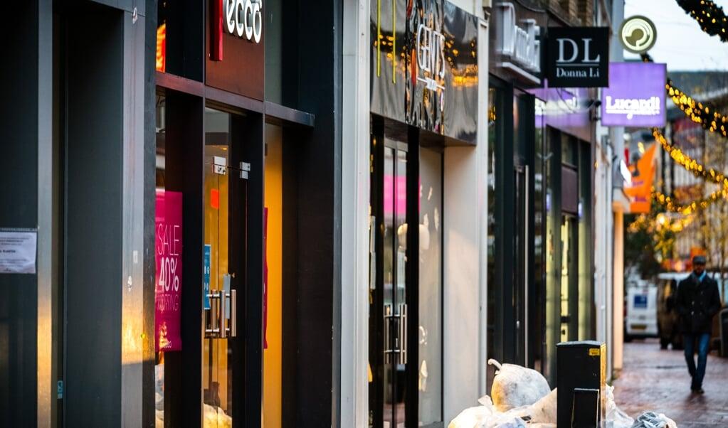 Dichte winkels en een nagenoeg verlaten winkelstraat in de binnenstad van Eindhoven. Niet-essentiële winkels moesten de deuren sluiten.  (beeld anp / Rob Engelaar)
