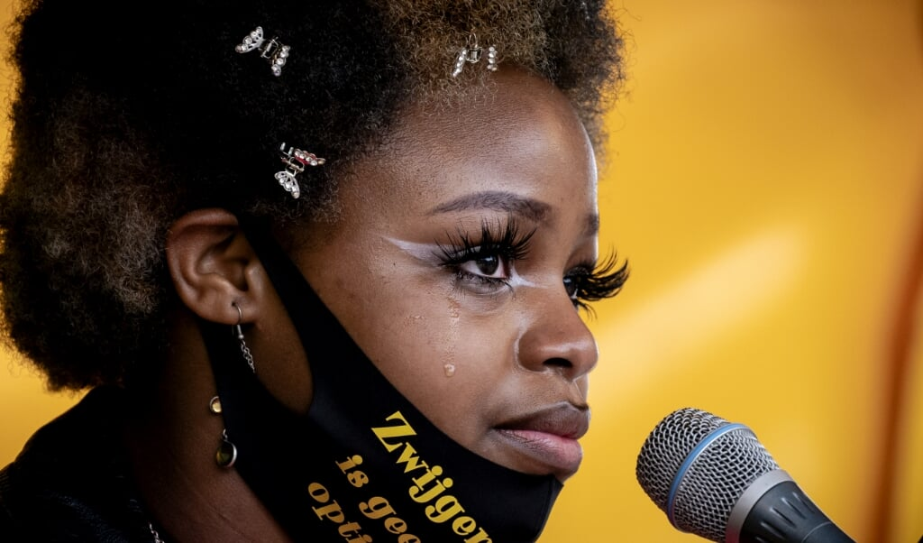 Een spreekster op het podium tijdens een demonstratie tegen racisme, eerder deze maand. Mensenrechten- en klimaatorganisaties organiseerden het protest na een reeks discriminerende acties.  (beeld anp / Sander Koning)