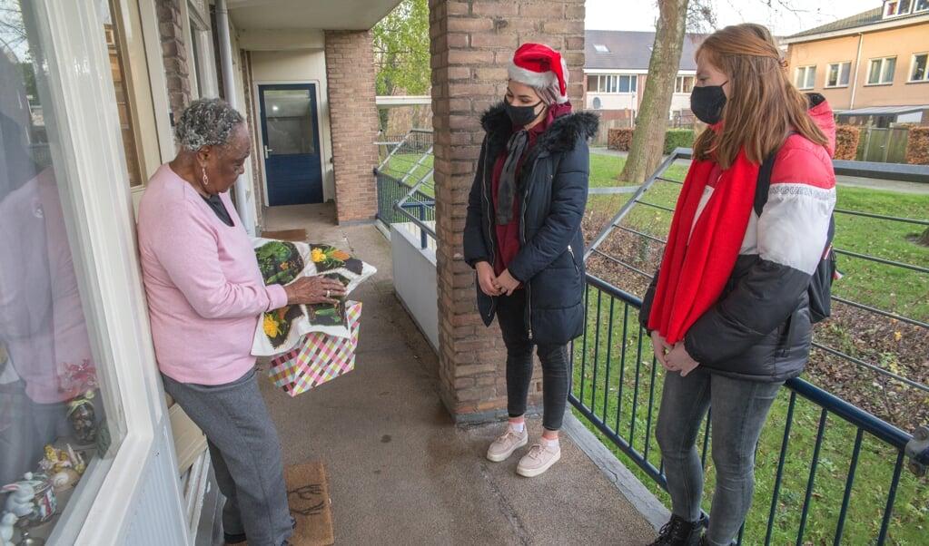 De tachtigjarige Dorothy Kingsale bekijkt de inhoud van de verrassingstas van Sahla Lograda en Joy de Blok.  (beeld Hans-Lukas Zuurman)