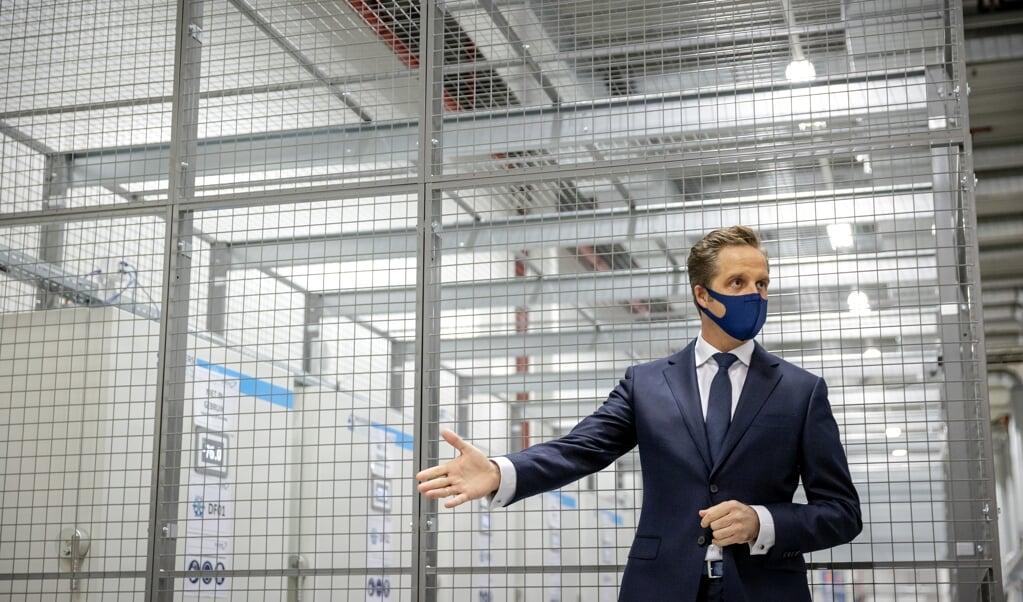 Minister Hugo de Jonge (Volksgezondheid, Welzijn en Sport) staat de pers te woord met in de achtergrond de ultra-low freezers bestemd voor vaccins bij Movianto Nederland tijdens een werkbezoek aan de locatie voor opslag van vaccinaties tegen COVID-19.   (beeld anp / Robin van Lonkhuijsen)