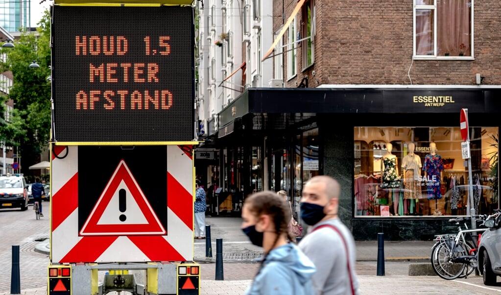 Een bord met informatie over mondkapjesplicht tegen het coronavirus in het centrum van Rotterdam.  (beeld anp / Sander Koning)