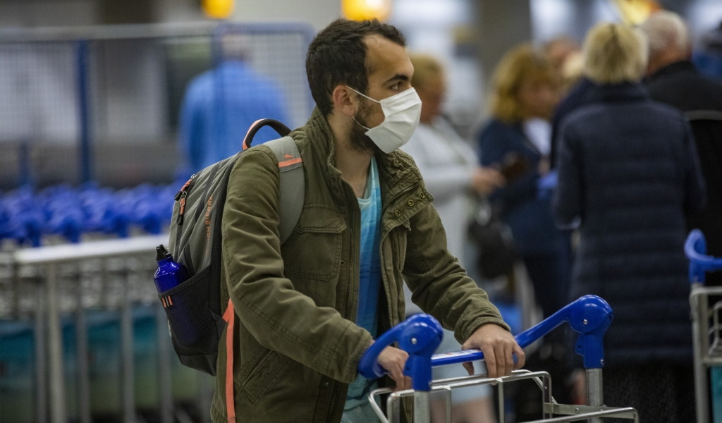 Nederlandse passagiers van het cruiseschip de Westerdam arriveren op Schiphol. De Nederlanders zijn negatief getest op het coronavirus en mochten daarom terug naar Nederland.  (beeld anp / Michel van Bergen)