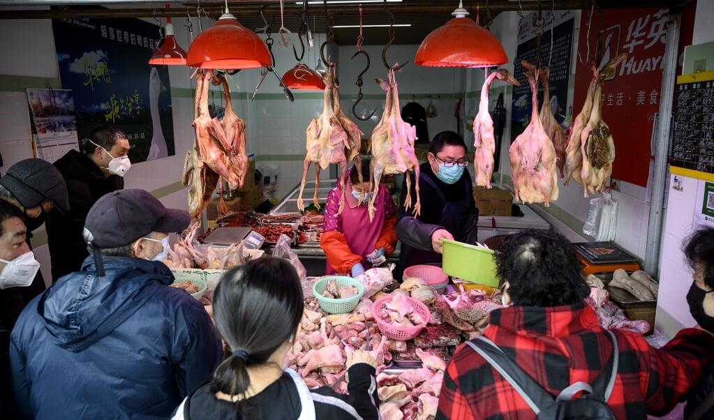 Mensen winkelen met beschermende gezichtsmaskers bij een kippenkraam op een 'natte markt' in Shanghai. Op zo'n natte markt worden kippen geslacht, wat het risico op blootstelling aan bacteriën en virussen zoals COVID-19 vergroot.  (beeld afp / Noel Celis)