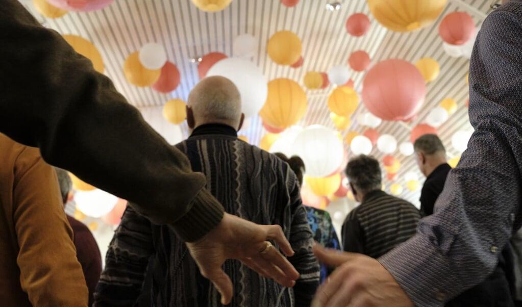 Afgevaardigden van de vrijgemaakt-gereformeerde synode en de Nederlands-gereformeerde landelijke vergadering zongen hand in hand, nadat ze unaniem hadden besloten voort te gaan op de weg van eenwording.  (beeld Dick Vos)