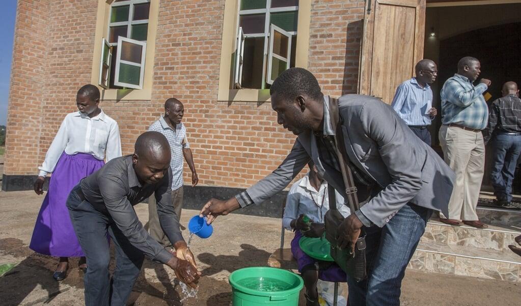 Kerkgangers in Malawi wassen bij de ingang van de kerk hun handen tegen het coronavirus. Wanneer moet je als zendingsorganisatie uit een land als Malawi je mensen terughalen?  (beeld afp / Amos Gumulira)