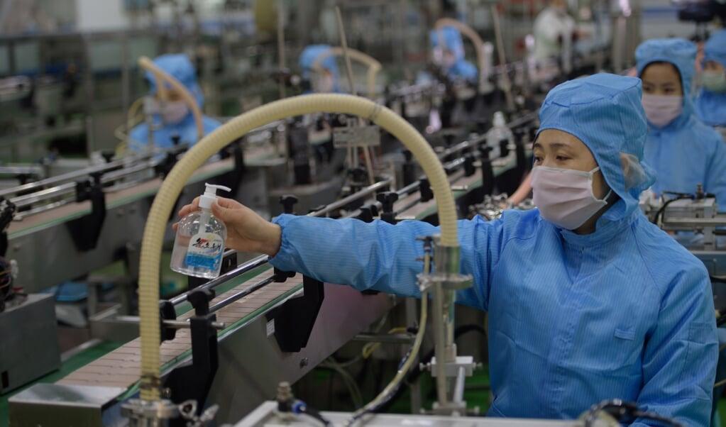 Een arbeider controleert de productie van flesjes desinfecterende vloeistof in zeepfabriek Ryongaksan in de Noord-Koreaanse hoofdstad Pyongyang.  (beeld afp / Kim Won Jin)