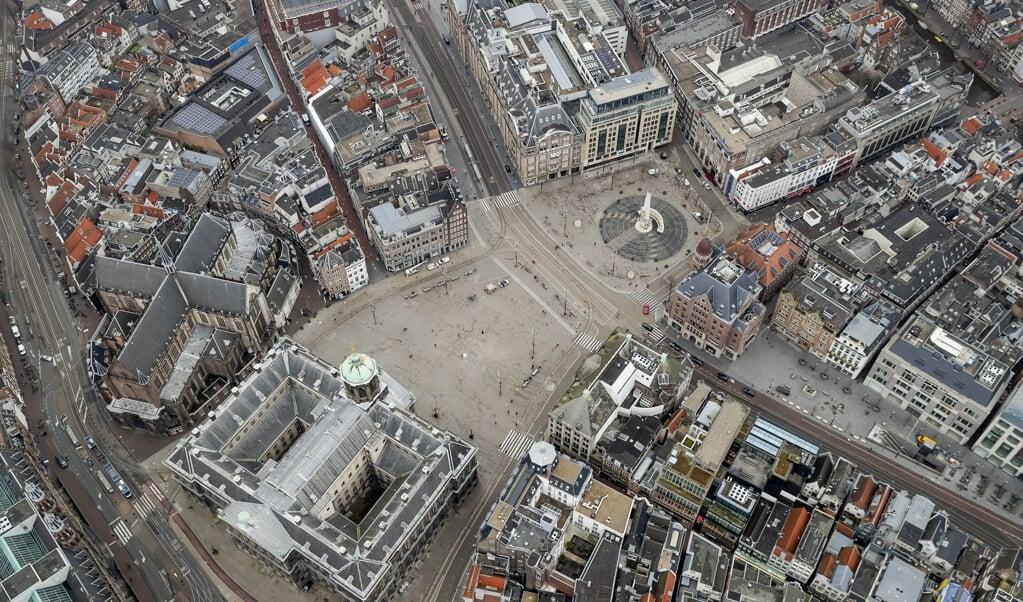 Luchtfoto van een vrijwel lege Dam in Amsterdam. Nu volgen mensen de regels goed op, maar als de coronacrisis lang gaat duren, kan er onrust ontstaan.  (beeld anp / Robin van Lonkhuijsen)