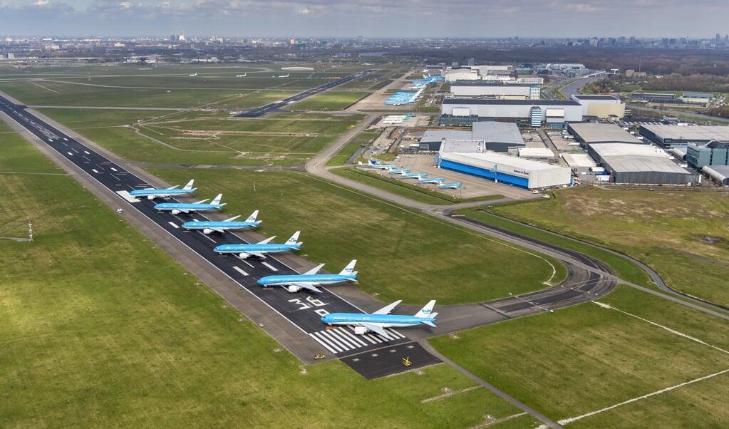 Vliegtuigen van de KLM staan werkeloos geparkeerd op de Aalsmeerbaan.   (beeld anp / Peter Bakker)