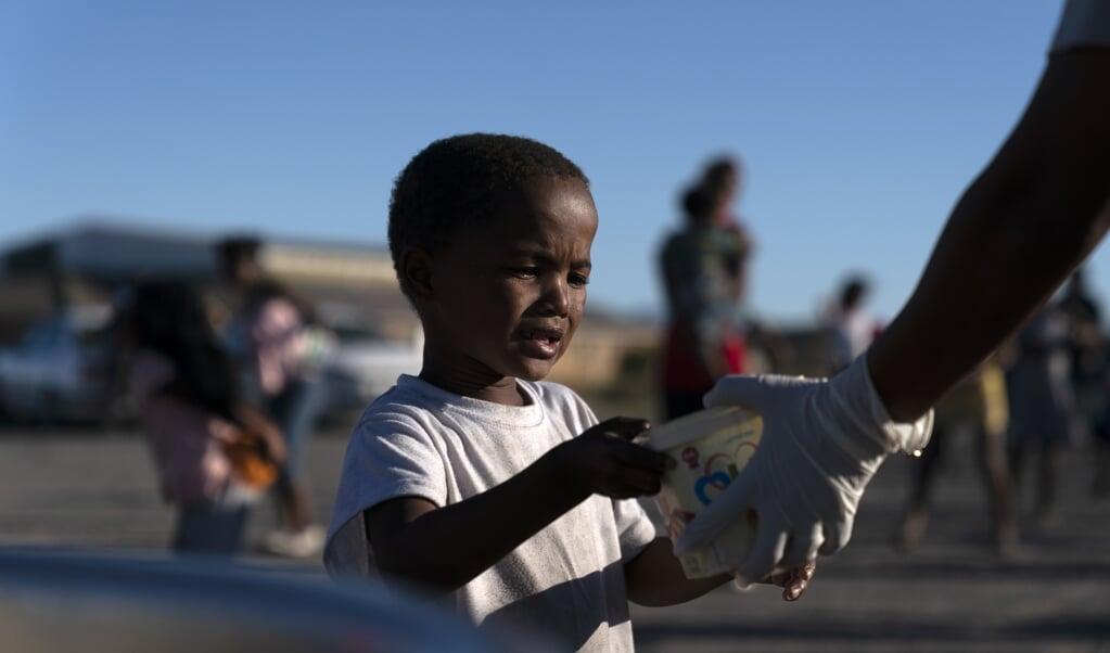 Een Zuid-Afrikaanse jongen in Kaapstad krijgt voedsel uitgereikt. Inwoners die niet kunnen werken door de lockdown, krijgen nu ook een geldbedrag.   (beeld epa / Nic Bothma)