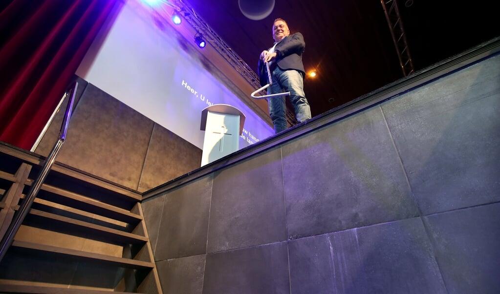 Dominee Gerke Oostra met zijn attribuut voor de doop op anderhalve meter afstand ten tijde van corona.  (beeld persburo Melissen)