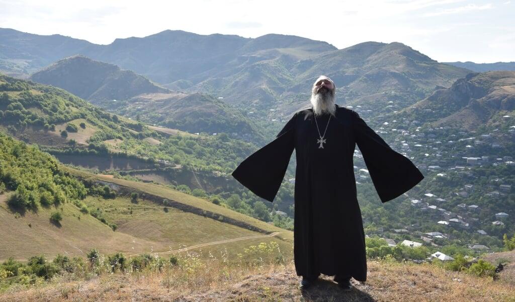Een priester bidt voor vrede in het plaatsje Movses, op de grens tussen Armenië en Azerbeidzjan, nadat bij grensconflicten zeker 16 mensen om het leven kwamen.   (beeld afp / Karen Minasyan)