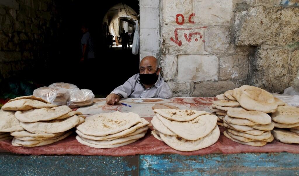 Een Palestijnse broodverkoper in Nablus op de Westelijke Jordaanoever.  (beeld Epa/alaa Badarneh)