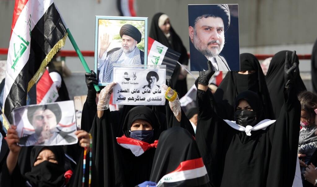 Aanhangers van de Irakese leider Muqtada al-Sadr houden op 27 november 2020 Irakese vlaggen en diens portret omhoog. Al Sadr pleitte de afgelopen weken voor politieke hervormingen en strijd tegen corruptie in het land.   (beeld Epa / Ahmed Jalil)