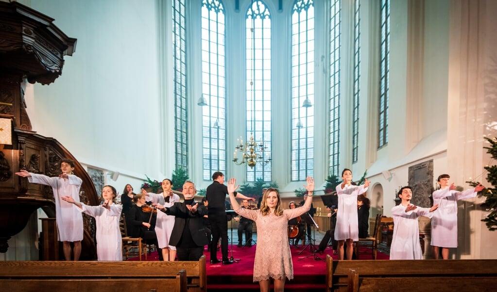 Almatine Leene, de Theoloog des Vaderlands, met achter en naast haar de dansers van de Dutch Don't Dance Division en de leden van het Kloosterkerk-Ensemble en Collegium Delft onder leiding van dirigent Daniel Rouwkema.  (beeld eo / Willem Jan de Bruin)