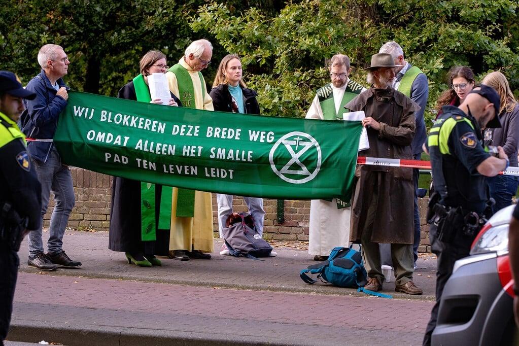 De politie haalde een groep voorgangers over de rijweg te verlaten en op de stoep te gaan staan waar zij in gebed gingen.  (beeld Dirk Hol)
