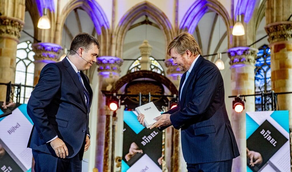 Koning Willem Alexander neemt in de Grote Kerk het eerste exemplaar van de NBV21, de vernieuwde Nieuwe Bijbelvertaling, in ontvangst. Koning Willem Alexander is beschermheer van het Nederlands-Vlaams Bijbelgenootschap.  (beeld anp / Royal Images Robin Utrecht)