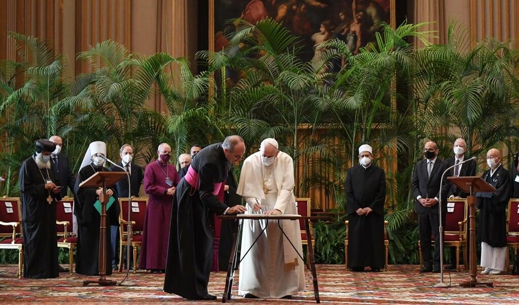 Paus Franciscus ondertekent de oproep van internationale religieuze leiders en wetenschappers voor klimaatactie.  (beeld epa / Alessandro Di Meo)