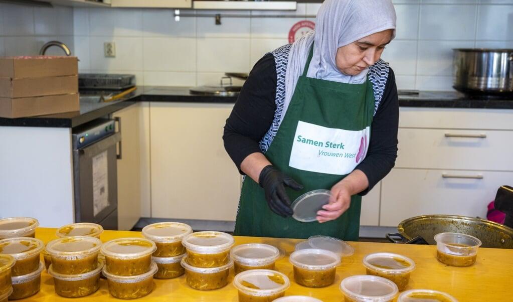 Een vrijwilliger pakt een maaltijd in die de stichting Samen Sterk Vrouwen West uitdeelt aan minderbedeelden.  (beeld anp / Evert Elzinga)