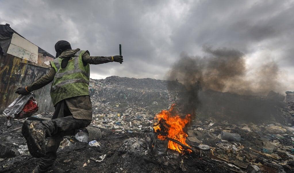 Een jongeman verbrandt een motor om koper te winnen op de Dandora-vuilnisbelt in Nairobi.   (beeld epa / Dai Kurokawa)
