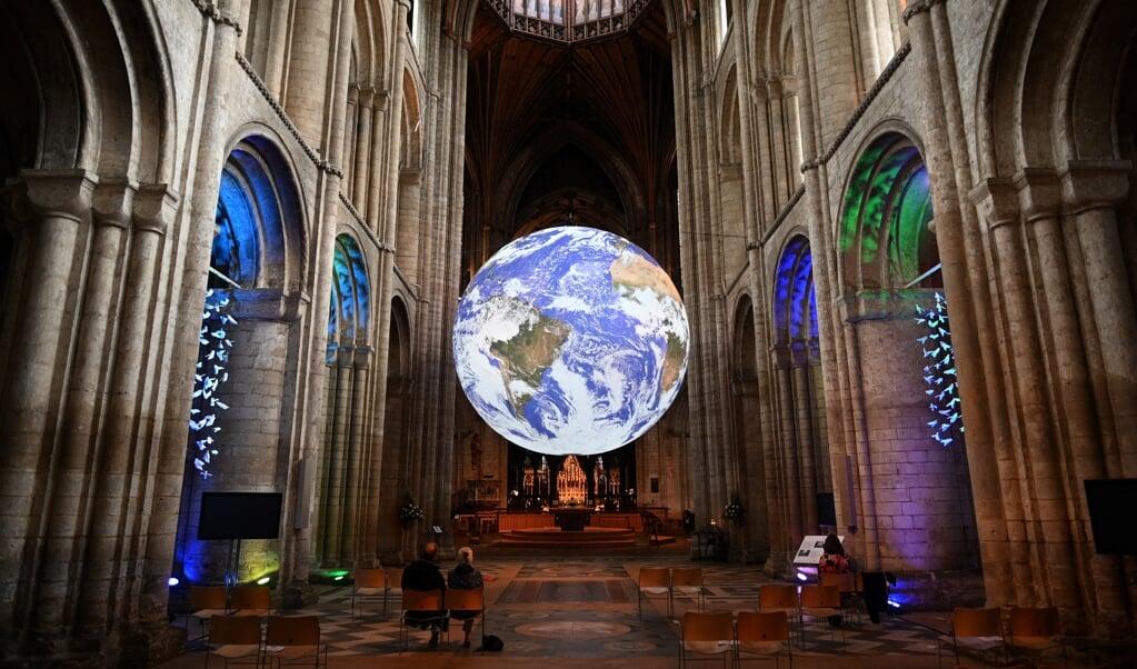 Een zeven meter grote aarde van de  Britse artiest Luke Jerram in de kathedraal van Ely. Maar de lichtblauwe planeet wordt donkerder, door afname van het wolkendek.  (beeld afp / Oli Scarff)