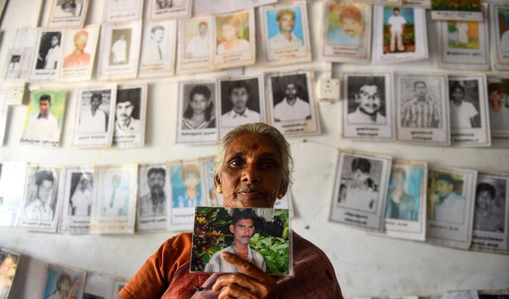 Een vrouw uit de Tamil-gemeenschap in Sri Lanka houdt een foto omhoog van een geliefde die is verdwenen tijdens de burgeroorlog.  (beeld afp / Kodikara)