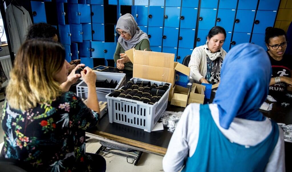 Statushouders aan het werk bij een re-integratiebedrijf. Het is lastiger fondsen werven voor hulp aan deze groep.  (beeld anp / Jerry Lampen)
