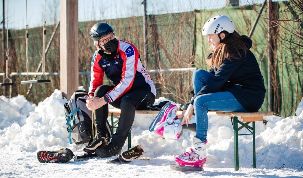 Schaatstrainer Hans Silvis met Aliene Boele op een bankje langs de ijsbaan in Ede. 'Zet een hoofddeksel op voordat je je schaatsen aandoet.'  (beeld Jorik Algra)