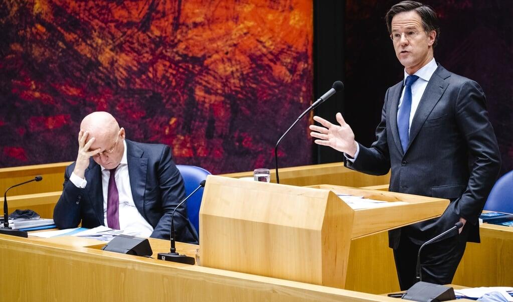 Ferdinand Grapperhaus, demissionair minister van Justitie en Veiligheid, en demissionair premier Mark Rutte tijdens het debat in de Tweede Kamer over de nieuwe spoedwet over de avondklok.  (beeld anp / Sem van der Wal)