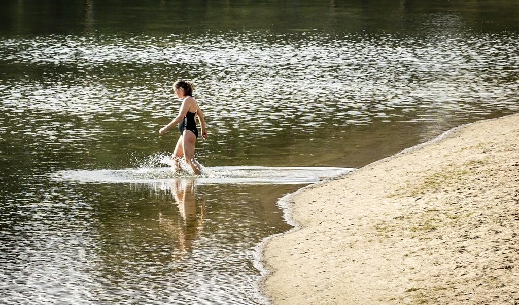 Vroege lente in Nederland: in badkleding het Henschotermeer in Woudenberg in, waar een week eerder nog ijs lag.  (beeld anp / Remko de Waal)