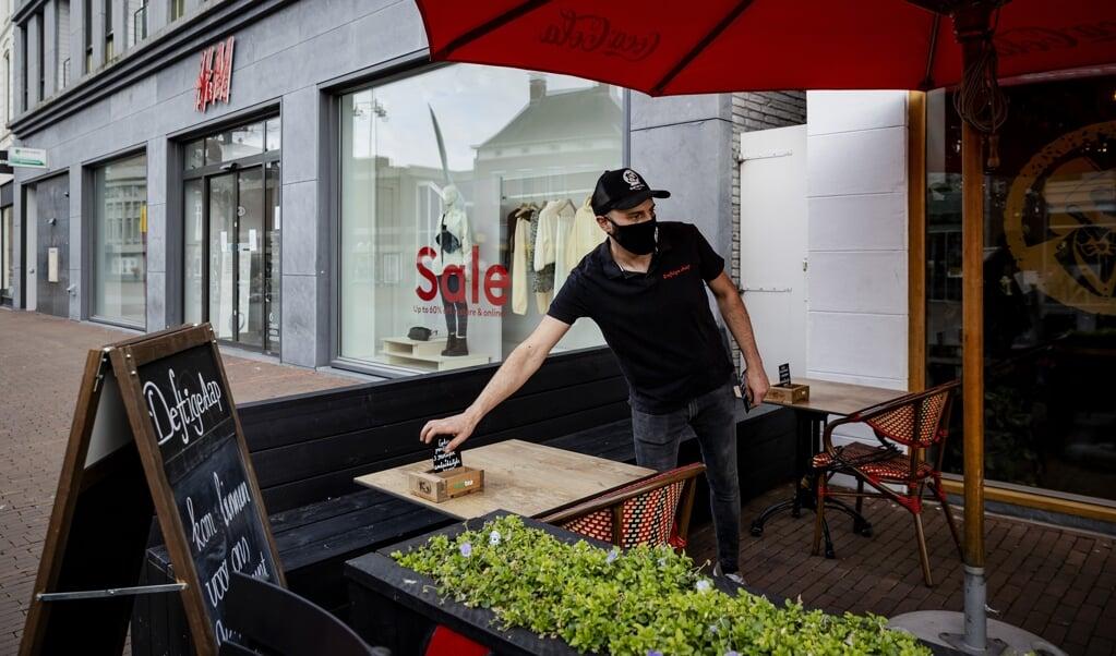 Een restauranteigenaar in Helmond bouwt zijn terras open. Verschillende horecazaken willen versneld open.  (beeld anp / Robin van Lonkhuijsen)